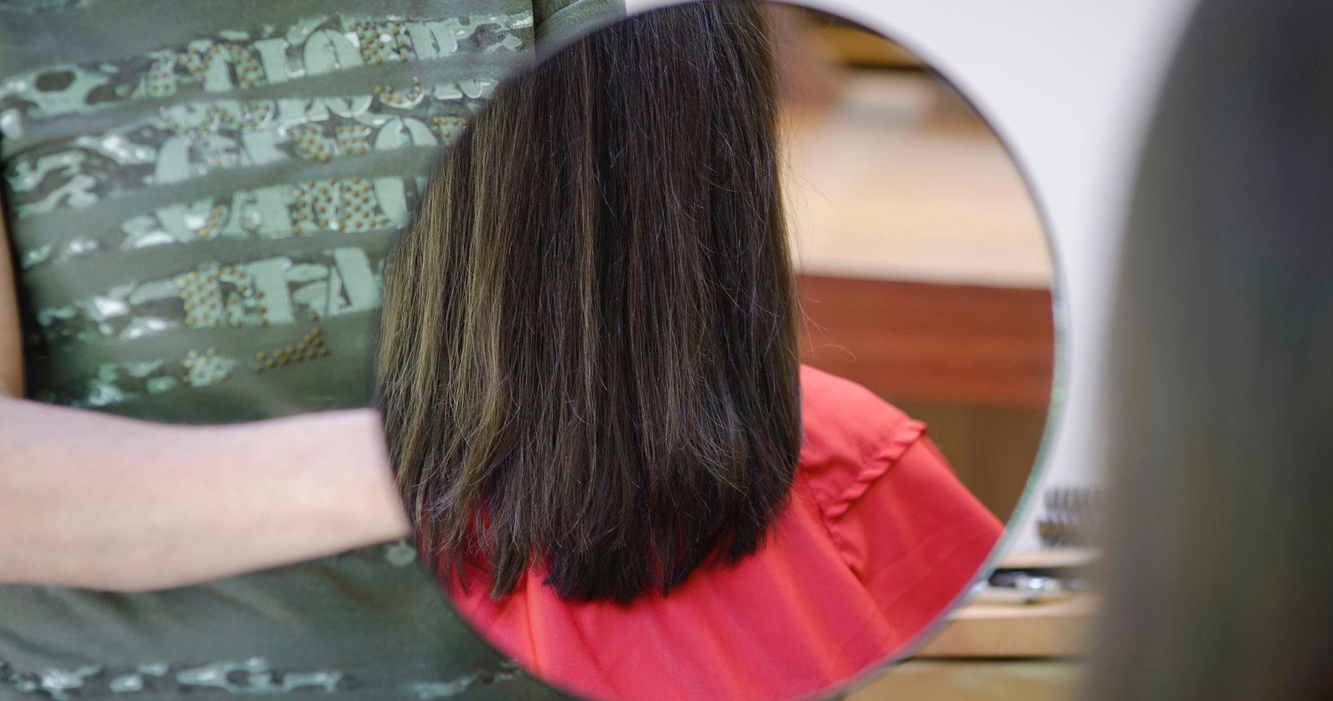Naturfriseurin zeigt ihrer Kundin der fertige Frisur im Spiegel
